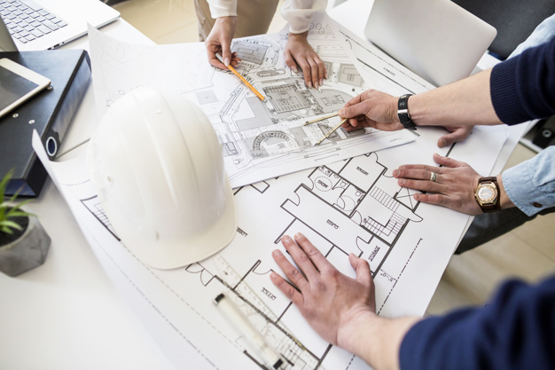 architects-engineer-discussing-at-the-table-with-blueprint_23-2147842977
